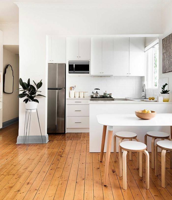 sol en planches de bois, tabourets blancs, îlot blanc, équipement de cuisine blanc, pot de fleur blanc