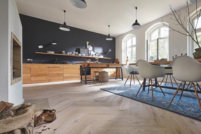 grande cuisine, sol cuisine bois franc, tapis bleu, mur noir, placards en bois, lampes industrielles, fenêtres arques