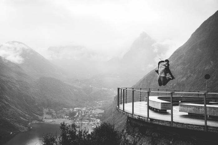 un homme sautant sur le fond des montagnes majestueuse et d'une vallée portrait noir et blanc l'homme et la nature