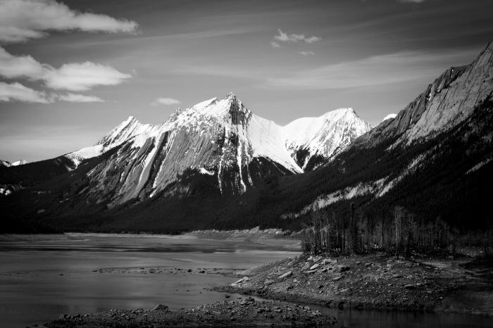 paysage noir et blanc des méandres d'une rivière au pied des pics enneigés de la montagne sous un ciel gris
