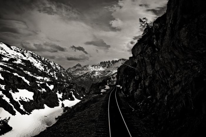 photographie noir et blanc de chemin de fer dans la montagne hivernal qui se faufile entre les rochers