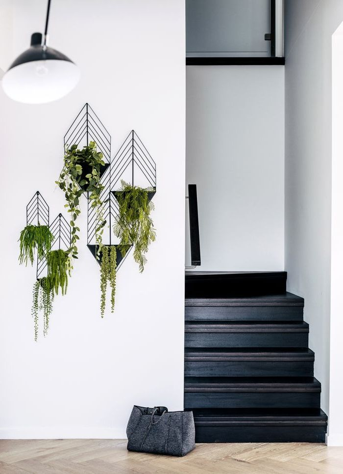 un escalier peint intégralement en noir pour un effet de profondeur, déco cage d'escalier d'esprit scandinave avec des porte-plantes en acier noir