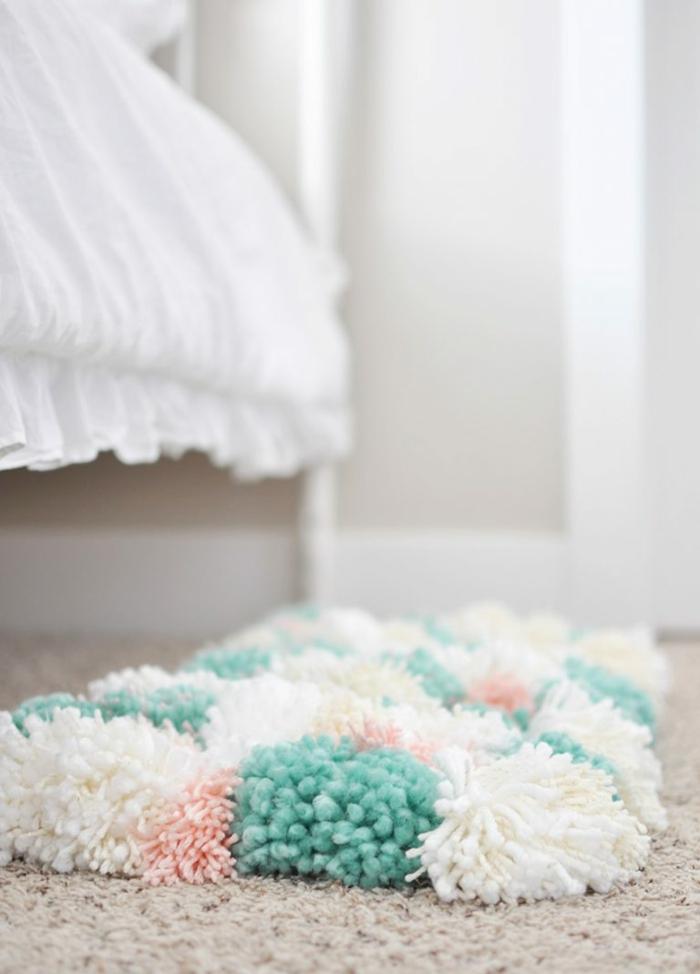 un tapis pompon épais disposé sous le lit, tapis aux couleurs blanc et turquoise, lit shabby