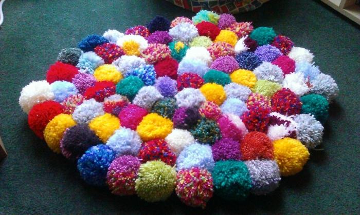 tapis laine bariolé, plusieurs pompons colorés assemblés ensemble en tapis rond moelleux