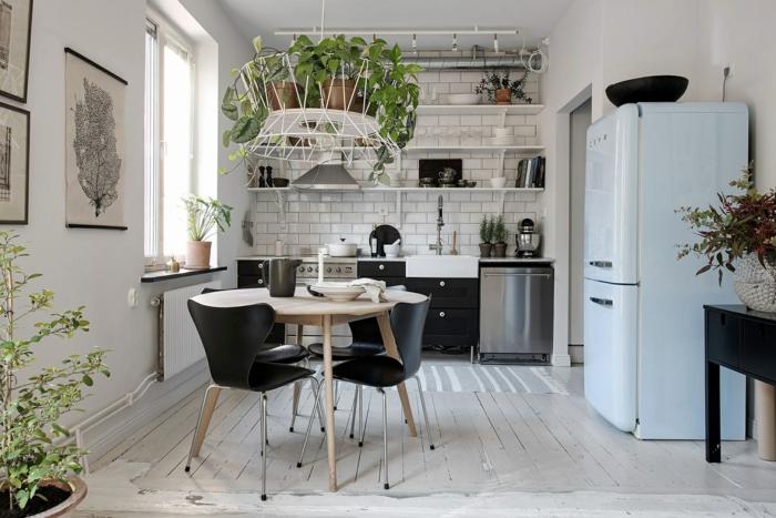 petite cuisine blanche, table ronde avec des chaises noires, parquet blanchi, réfrigérateur bleu pastel, étagères, carreaux métro, plusieurs plantes