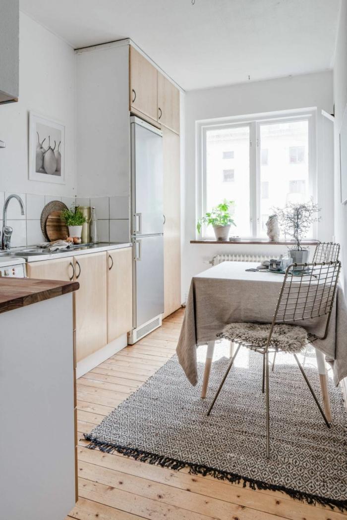cuisine gris clair, tapis gris rustique, chaises métalliques, murs bleu clair, fenêtre, pot de fleur sur le rebord