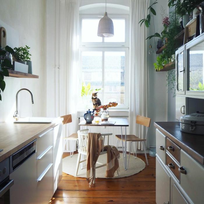 sol en bois laqué, rayons en bois, pots de fleurs, placards vintage, grande fenêtre avec rideau blanc, petite table carrée