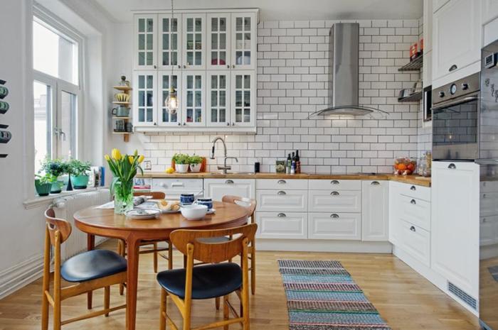 table ronde en bois, sol stratifié, carpette rayée, carrelage métro blanc, placard vitré suspendu, cuisine en l