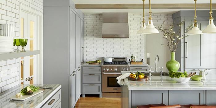 cuisine gris et bois, quatre lampes blanches, îlot de cuisine gris, carrelage métro blanc, vase vert