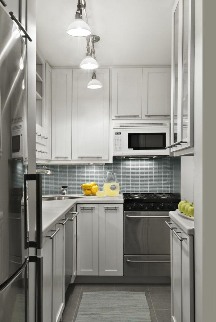 cuisine en longueur grise, lampes suspendues industrielles, aménager une petite cuisine, armoires gris clair, grand frigo chromé, fruits
