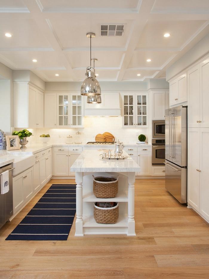 cuisine design industriel en bois et blanc, lampes chromées, îlot de cuisine avec rangement, tapis bleu, fours encastrables