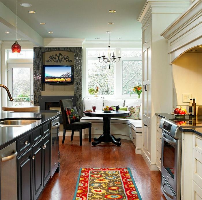 cuisine ouverte vers la salle à manger, tapis en couleurs joyeuses, placards gris, petite table noire