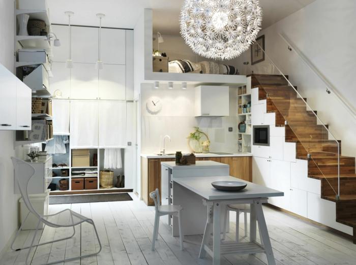 petit studio à deux niveaux, table blanche rabattable, grand plafonnier sophistiqué, étagère blanche, escalier mezzanine