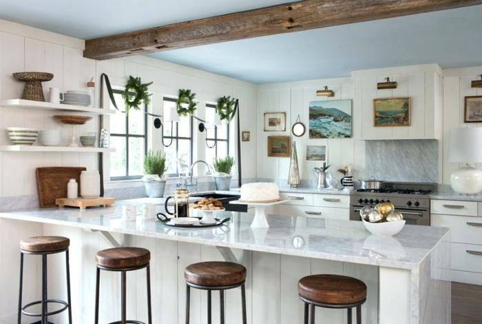 cuisine stylée en blanc et bois, poutre en bois au plafond, tabourets bois et métal, plafond bleu clair, étagères blanches