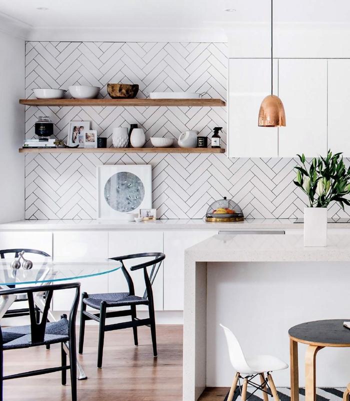 cuisine blanche super esthétique, table ovale en verre, chaises noires, rayons en bois, lampe cuivrée, armoires suspendues