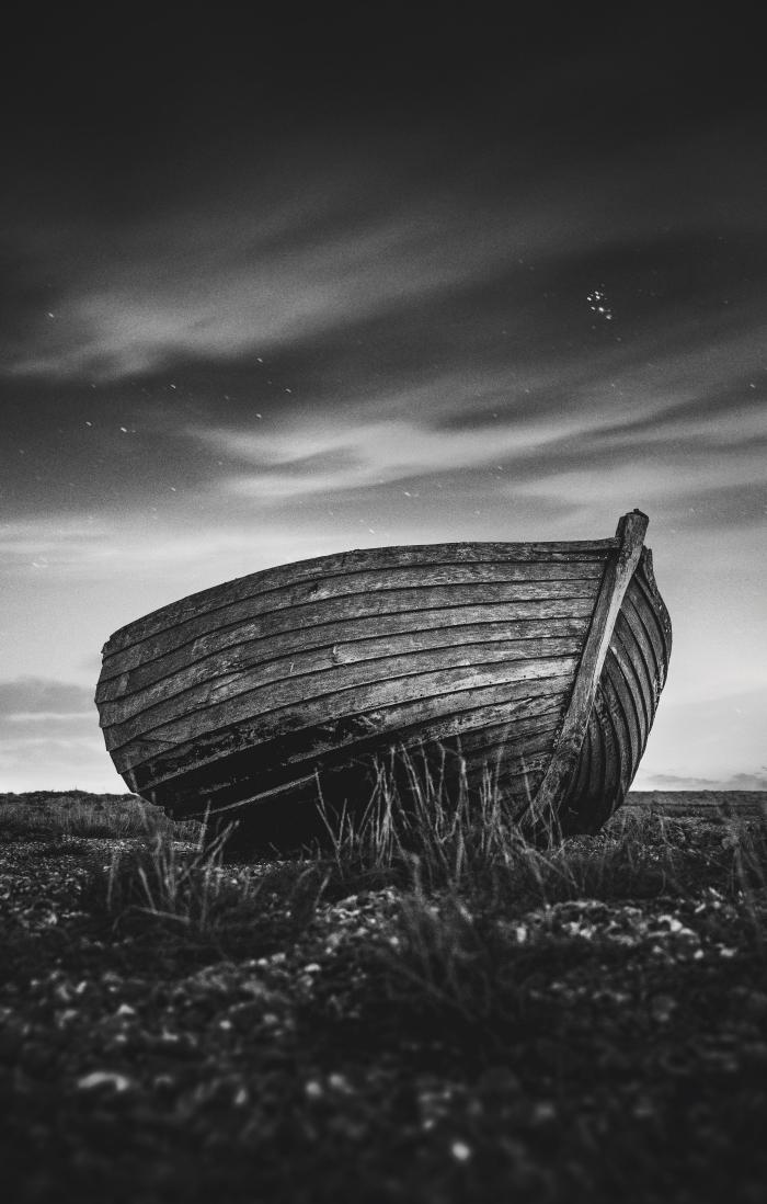 image noir et blanc poétique d'une barque solitaire abandonnée sur la rive sous les nuages dansant