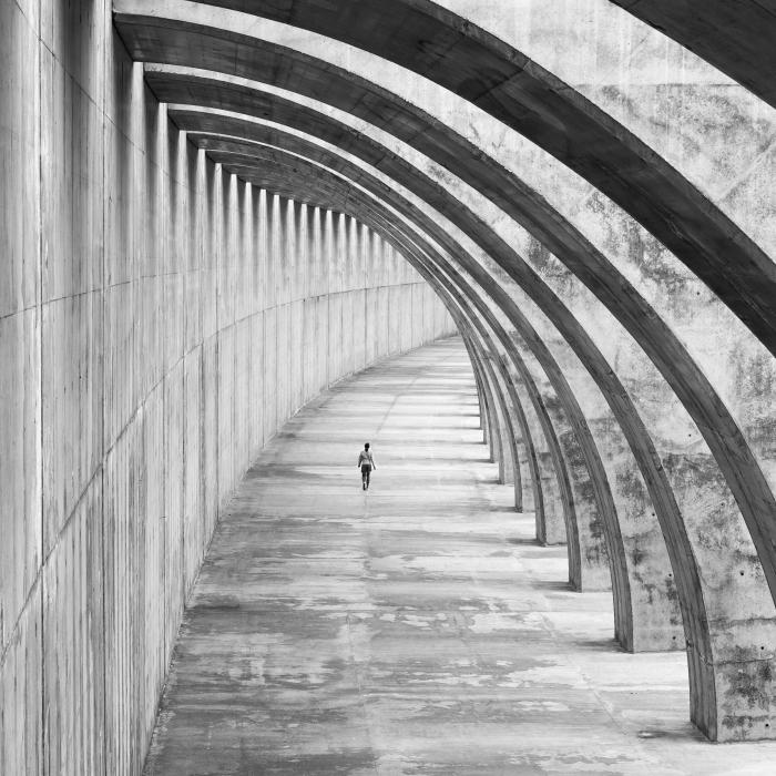 photo noir et blanc femme marchant sous un arc en béton, photo originale d'un bâtiment moderne