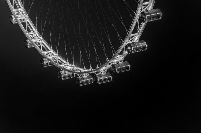 image noir et blanc d'une roue géante qui se détache sur le fond noir du ciel, exemple de photographie monochrome artistique