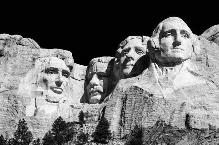 image noir et blanc de mont rushmore avec ses quatre présidents sculptés dans le rocher, se détachant sur le fond noir du ciel