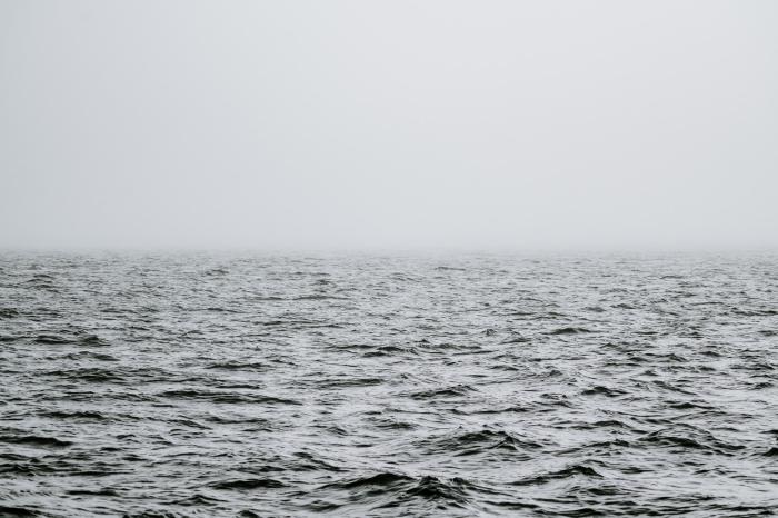 une photo noir et blanc de mer et l'horizon caché par le brouillard, photographie de paysage marin monochrome
