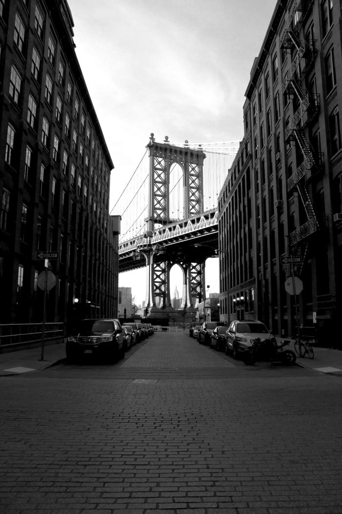 vue sur une partie du pont de new york entre de grands bâtiments, paysage urbain en noir et blanc pris d'une perspective originale