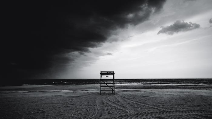 paysage marin en noir et blanc d'un plage déserte avec un poste de surveillance solitaire et un ciel orageux à demi couvert de nuages