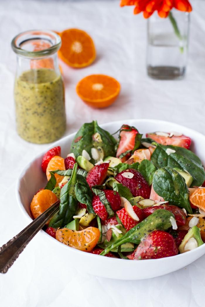 salade d'hiver avec fraises décongelées, feuilles d'épinards, mandarines en tranches, graines et purée de kiwi comme garniture