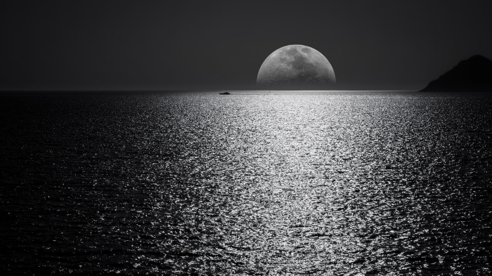 belle photo noir et blanc panoramique de la pleine lune émergeant du dessous de 'horizon et ses reflets sur la mer calme