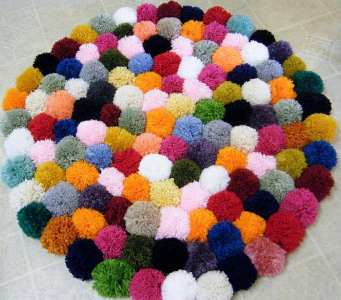 diy déco d'intérieur, pompons arrangés et attachés au toile canevas, modele de tapis multicolore
