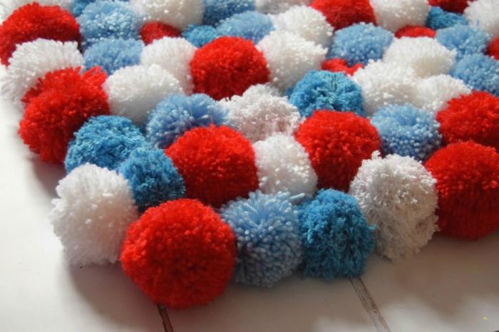 sol en planches peintes blanches, pompons bleus, blancs et rouges assemblés en joli tapis diy