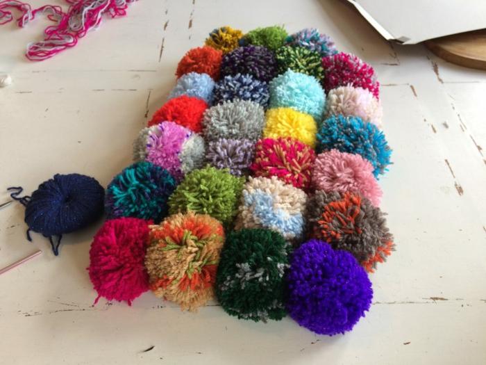 mélange de fils de laine pour faire un pompon en laine original, sol peint blanc, faire des pompons moelleux