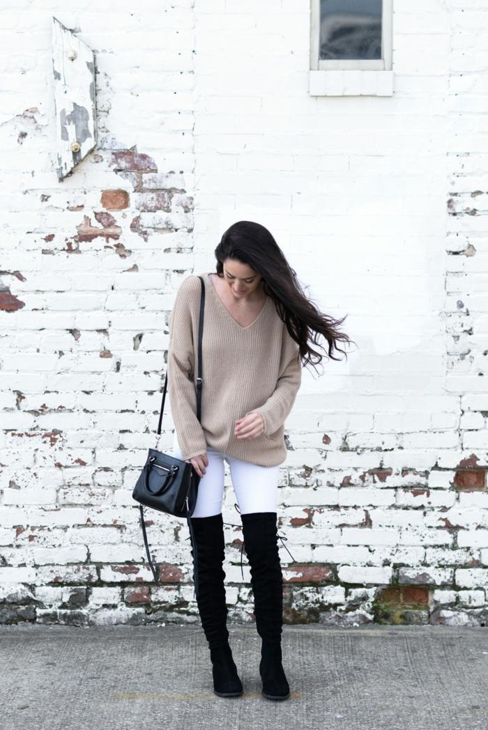 mur en briques peintes blanches, pull beige, décolleté triangulaire, sac noir, cuissardes, pantalon blanc