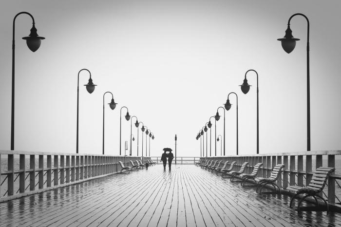 portrait noir et blanc d'un couple promenant son chien sur le quai sous le ciel gris, photographie monochrome