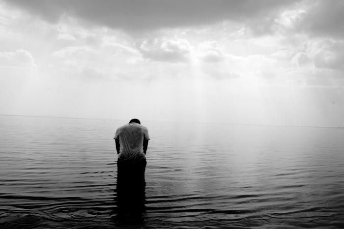 portrait noir et blanc le jeune homme et la mer, un homme la tête baissée, accroupi dos au rivage