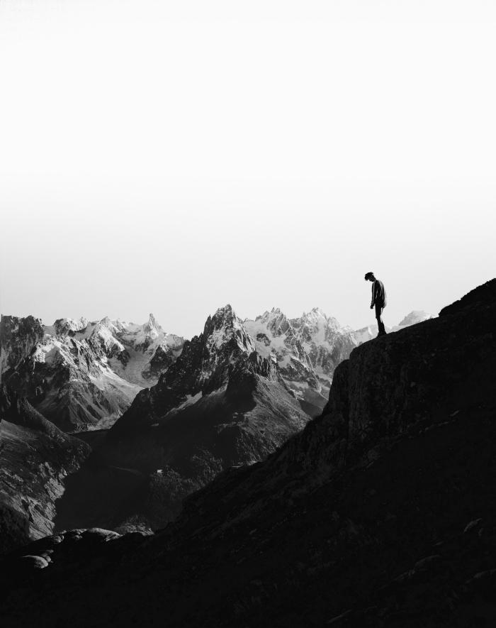 portrait noir et blanc l'homme et la montagne, photo en noir et blanc de silhouette d'un homme monté au sommet de la montagne