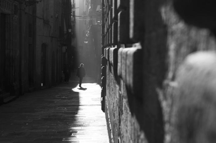 photographie noir et blanc de rue homme marchant dans une ruelle étroite et la lumière tombant sur une partie du pavement