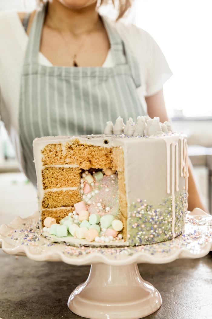 gâteau surprise à couches de génoise vanille, au glaçage coulant rempli d'un mix de poudre comestible, perles en sucre et guimauves