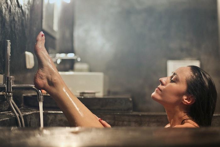 Prendre soin de ses cheveux en hiver, prendre un bain pas trop chaude, femme dans le baignoire