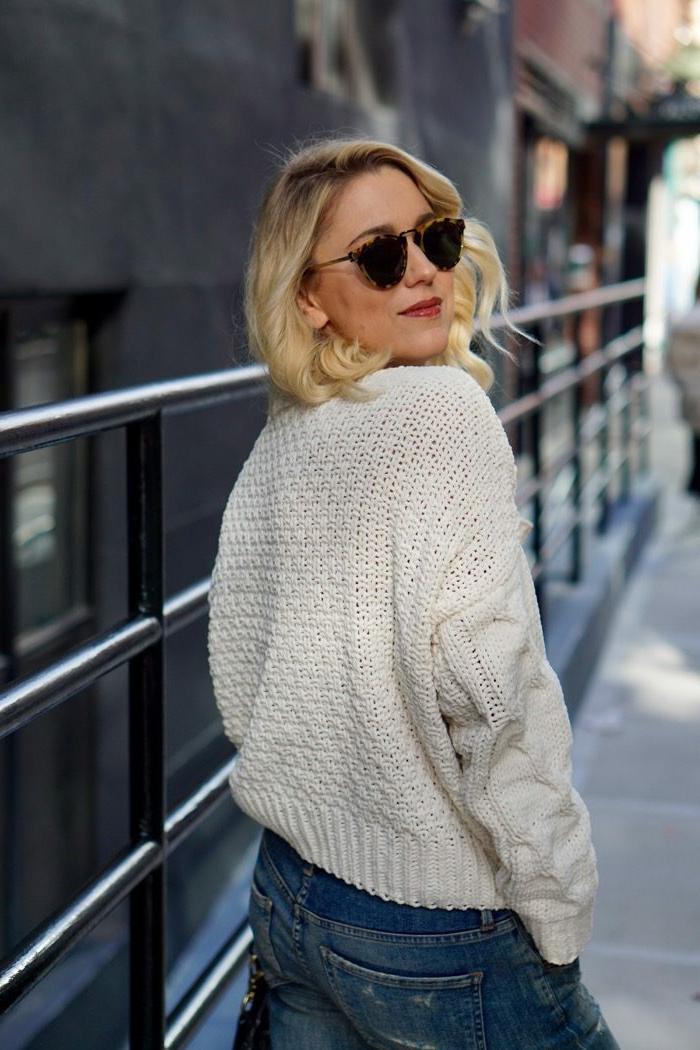 pull grosse maille femme, cheveux blonds bouclés, jeans bleus, lunettes tendance, pull loose femme