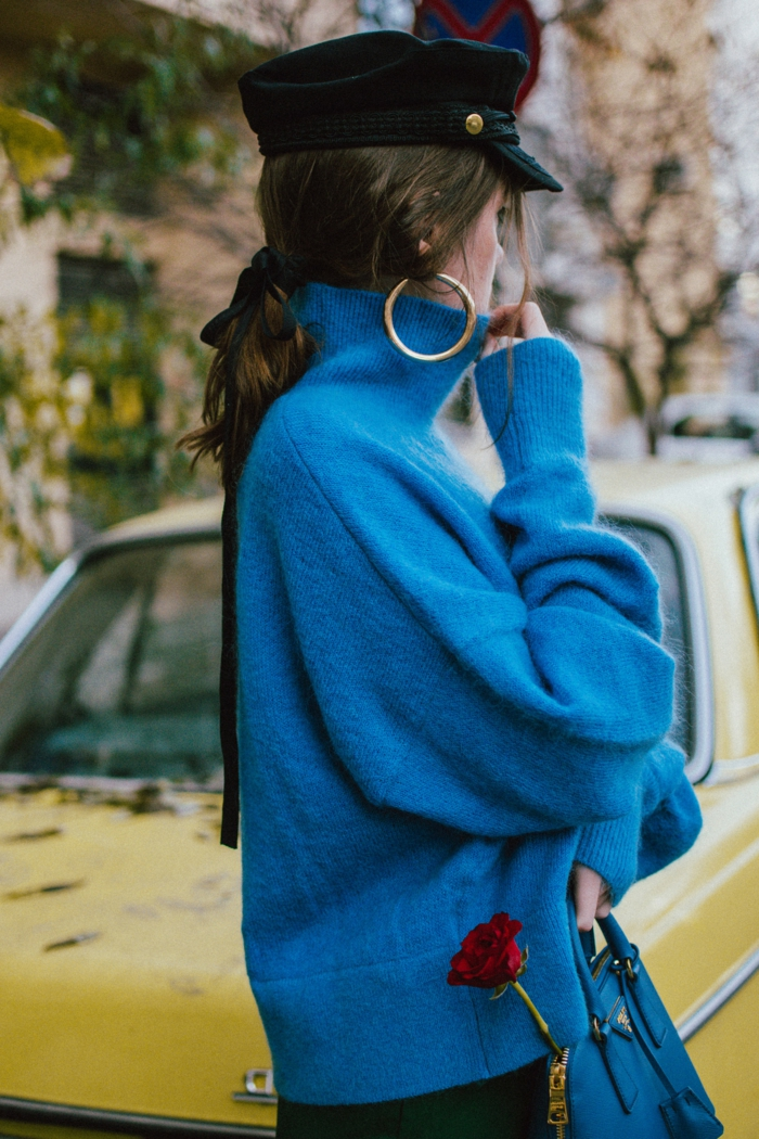 femme qui porte un pull bleu cobalt, casquette noire, pull col roulé rose rouge, créoles, pantalon vert