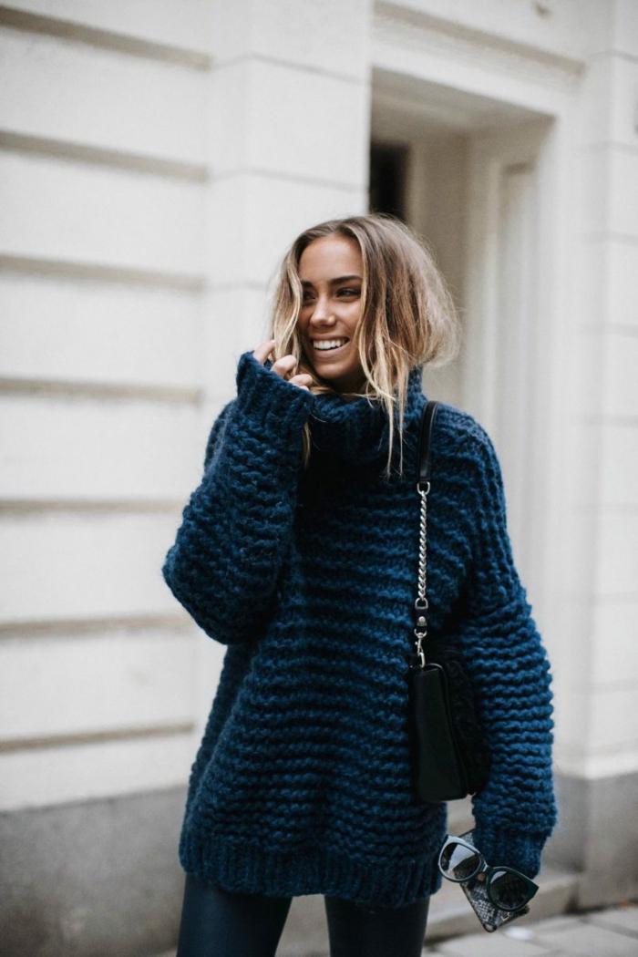 gros pull col roulé femme, sac noir, jeans bleus, cheveux blonds enfilés dans le pull