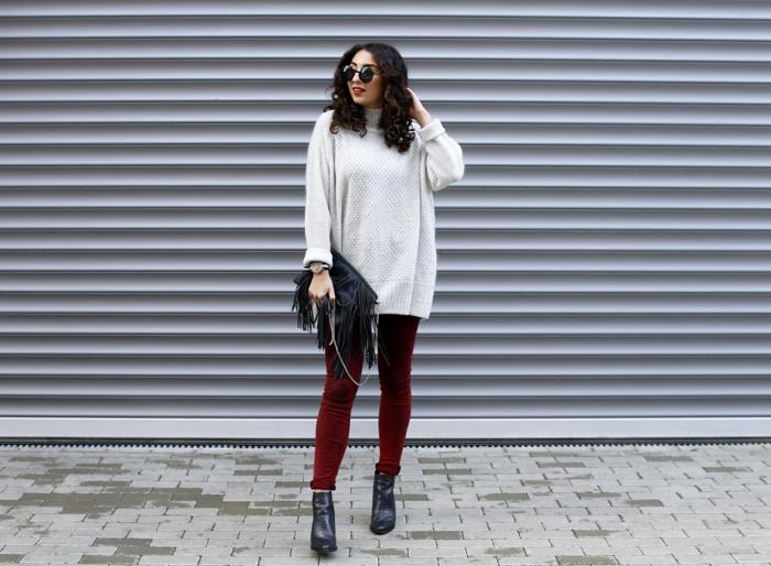 femme en pull oversize pour femme, pantalon slim rouge, bottes noires, cheveux bouclés, sac frangé