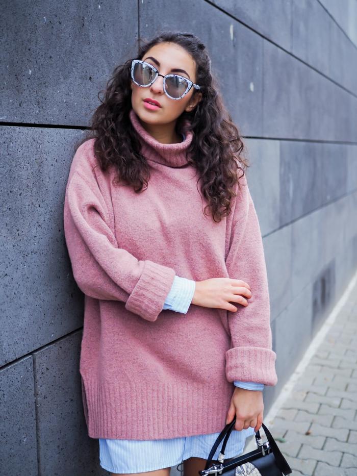 grand pull rose femme, lunettes monture bleue, chemise bleue sous le pull, sac noir