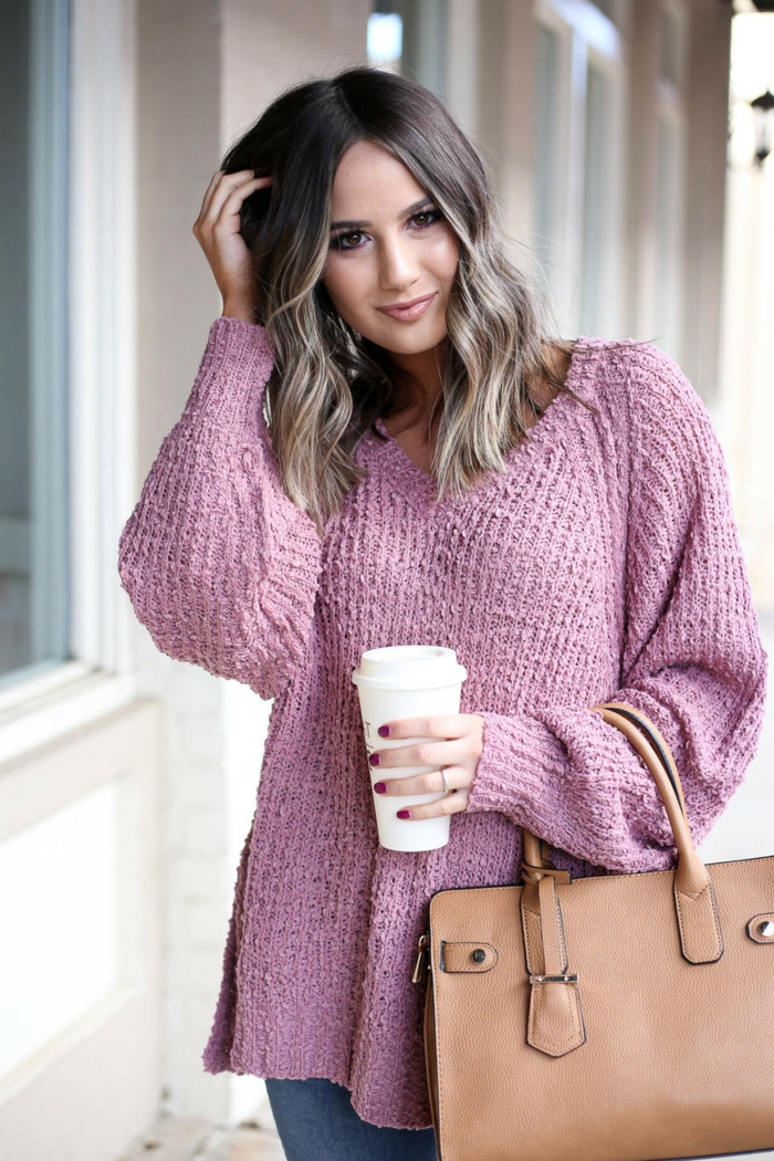 gros pull femme couleur mauve, sac couleur cognac, cheveux wavy, jeans bleus, tasse à café