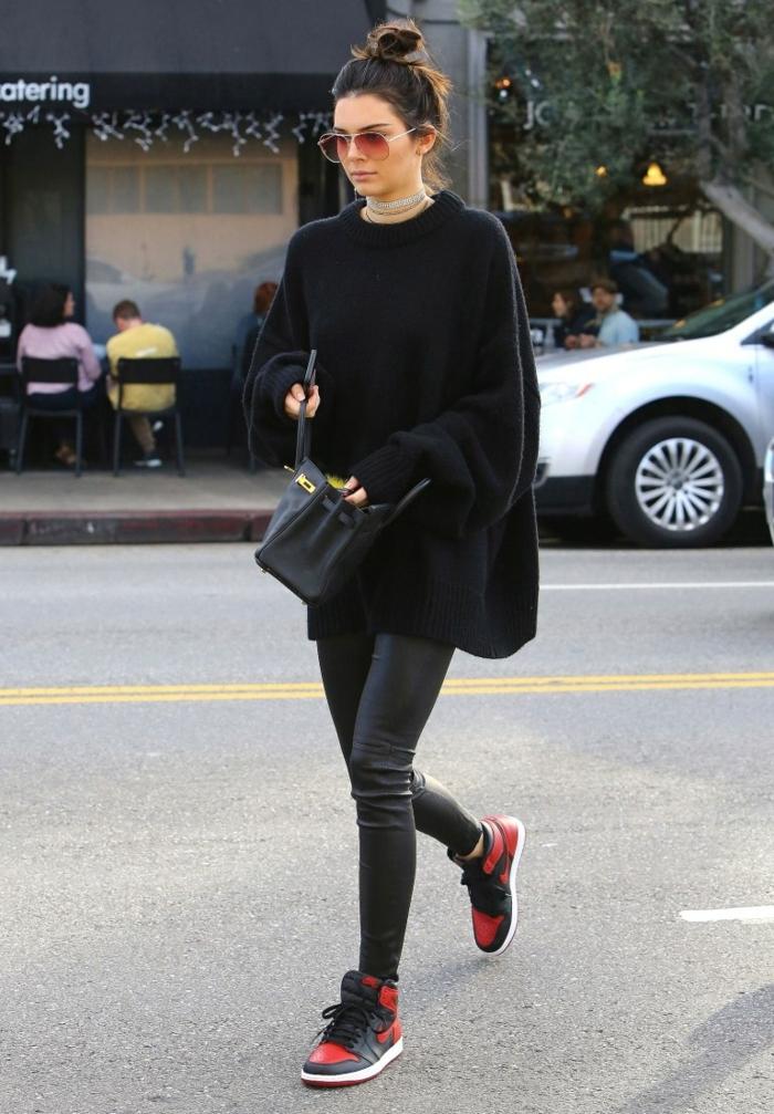 brunette qui porte des leggings en cuir, un pull en maille noir, lunettes chic, sac noir, chignon haut