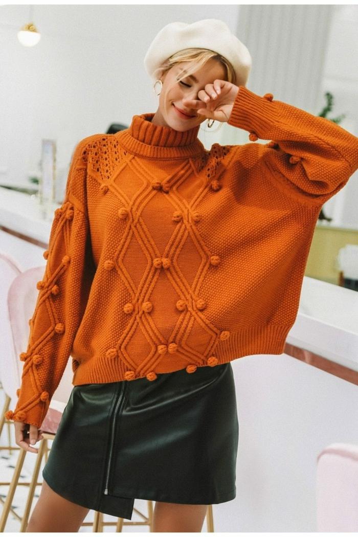 gros pull en laine orange, pull avec pompons, chapeau blanc, jupe en cuir, tenue femme chic