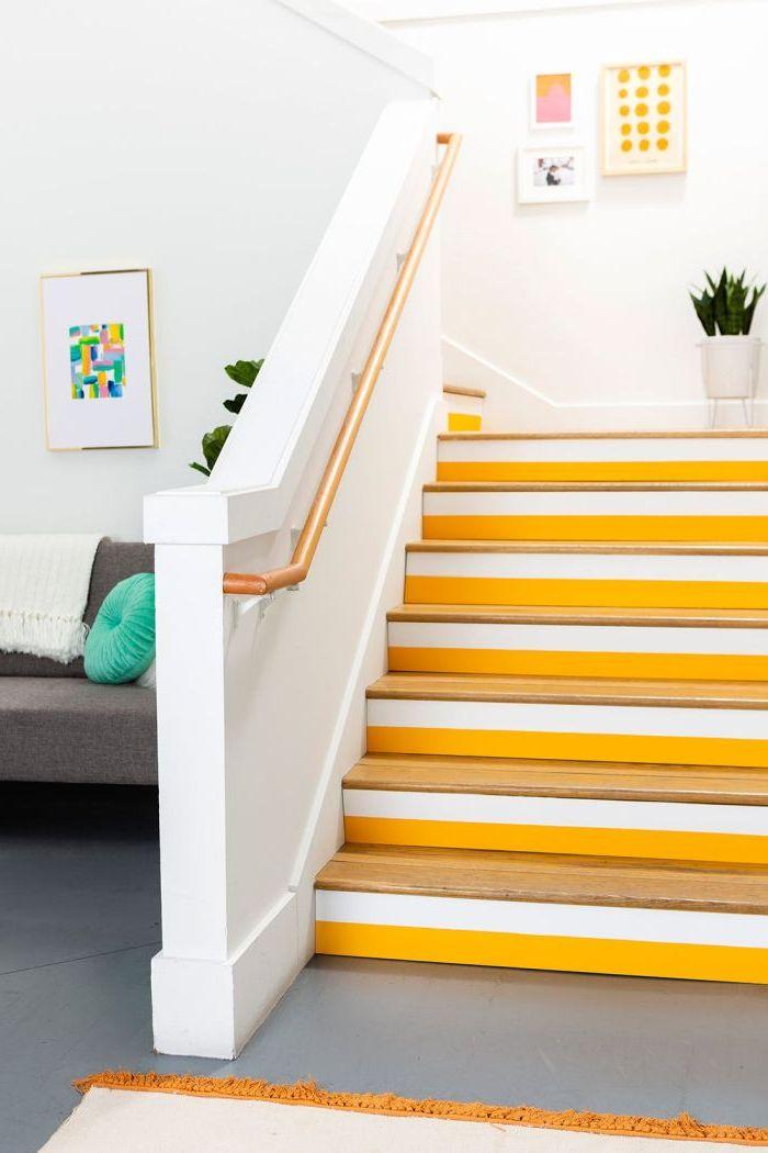 relooker un escalier en bois à l'aide de la peinture, des bandes de peinture jaune et blanche peintes sur les contremarches de l'escalier à l'aide de l'adhésif