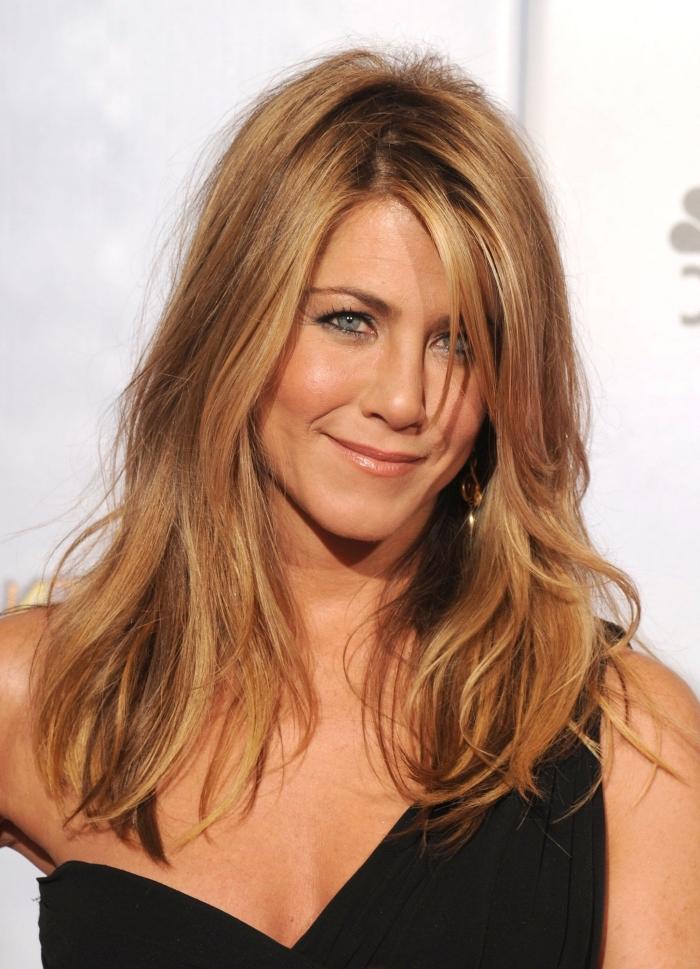 coiffure de Jennifer Aniston aux cheveux lâchés, exemple de balayage naturel sur brunette avec mèches cuivrés et reflets dorés