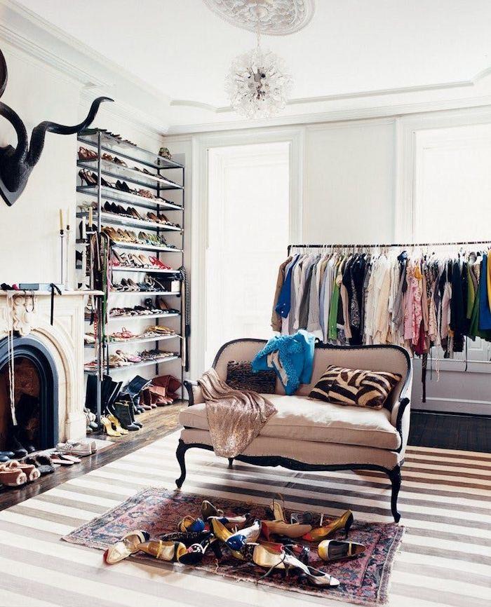 Vaste dressing de rêve avec un canapé au milieu et tapis magnifique devant, meuble rangement chaussures et un dressing pour les vetements, chambre penderie basse cool idée