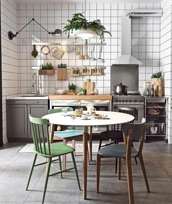 carreaux blancs, applique murale bras amovible, placards gris, petites étagères murales, tables blanches et chaises vintage